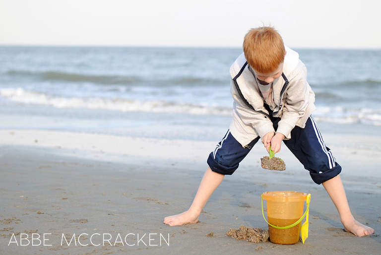 school boy shoveling beach sand at Isle of Palms, SC during Spring Break