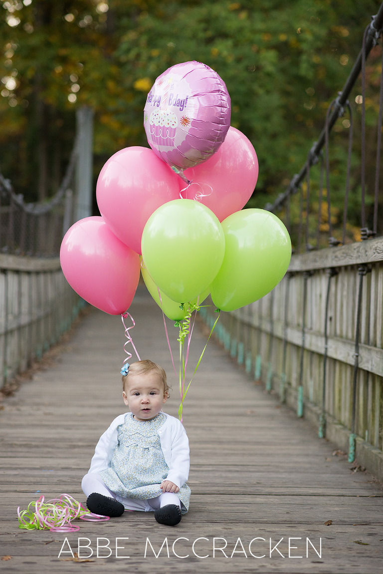 One year old birthday girl with colorful balloons