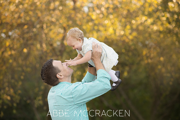 Daddy holding his one year old baby girl high in the air, sparkly bokeh behind them