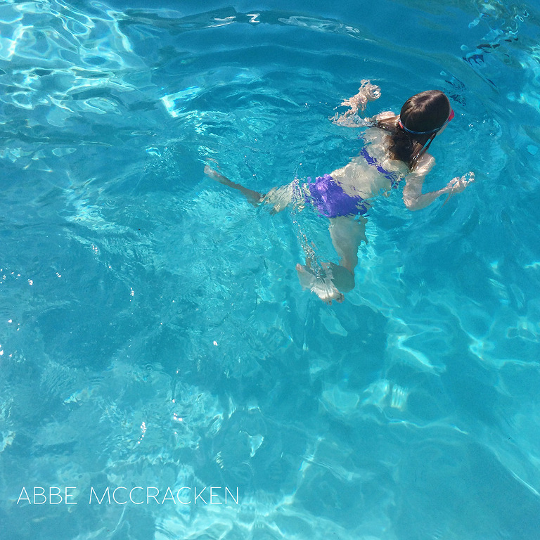 girl swimming in crystal clear blue pool taken with iPhone