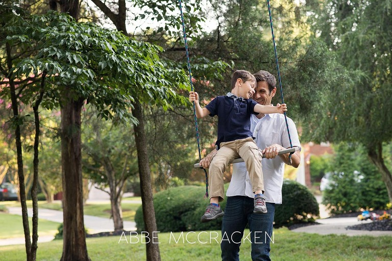 Summer family photo session - Father swinging his son in their Charlotte, NC front yard
