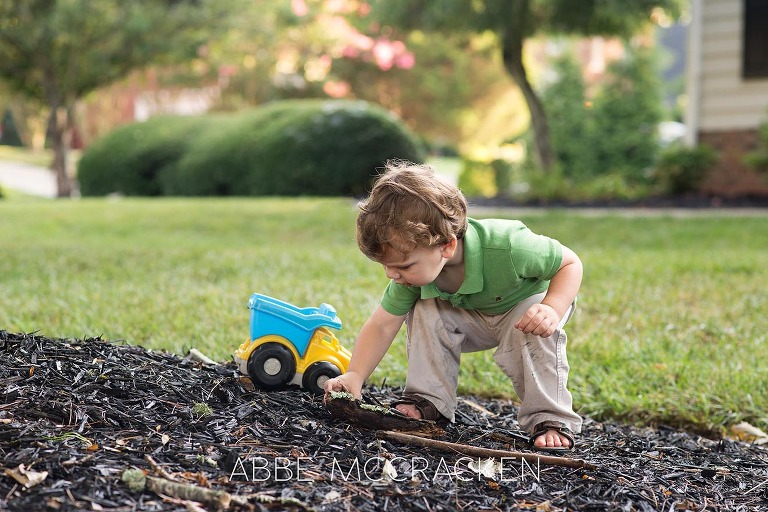 Toddler boy playing with a truck in his yard