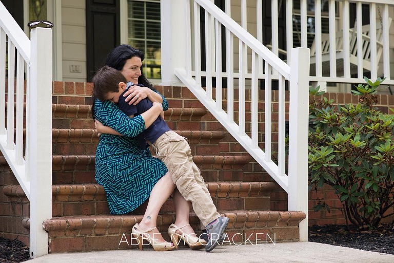 Summer family photography session - son hugging mom on their front steps