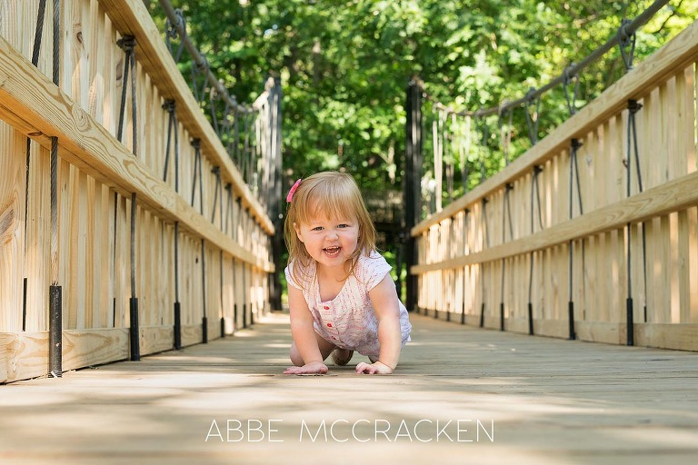two-year-old red-headed girl crawling on the newly rebuilt bridge in Charlotte's Freedom Park