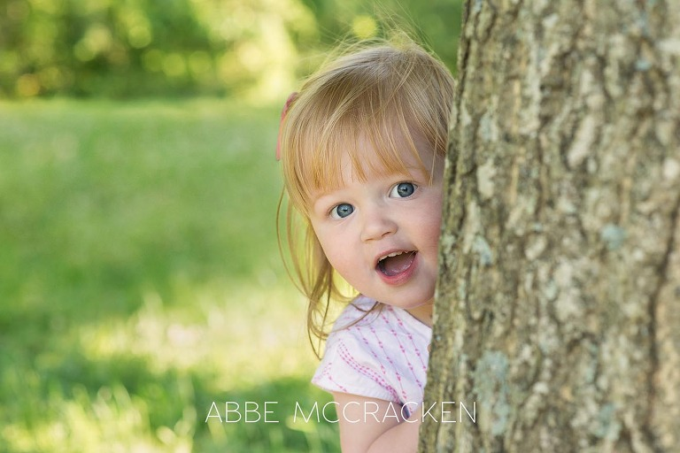 Adorable two-year-old girl played peek-a-boo with Charlotte NC child and family photographer Abbe McCracken