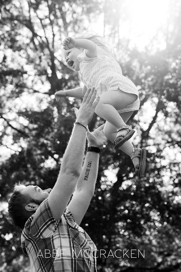 Family picture of a father tossing his two-year-old daughter into the air at Freedom Park