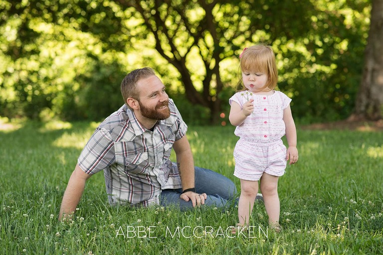 Picture of a father teaching is young daughter to blow dandelions.