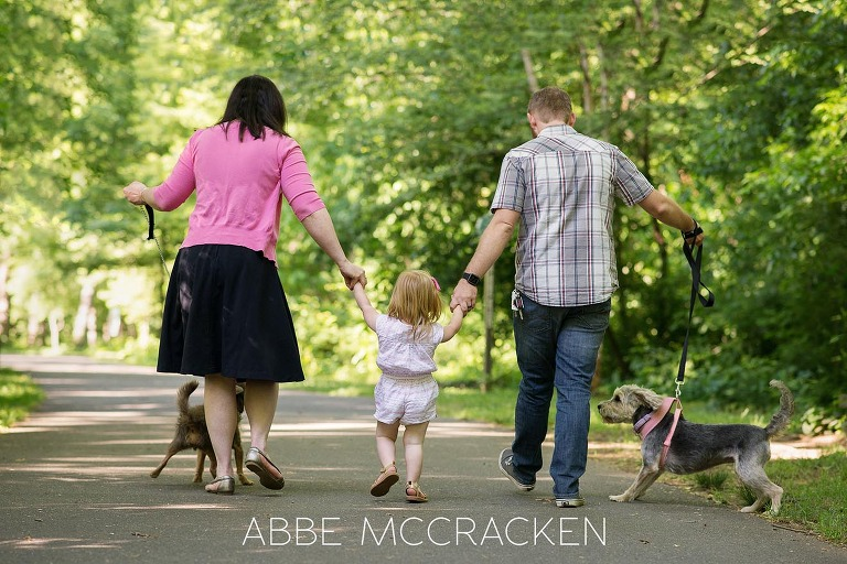Family of five - 3 humans, 2 dogs - walking on a paved trail in Charlotte NC's Freedom Park