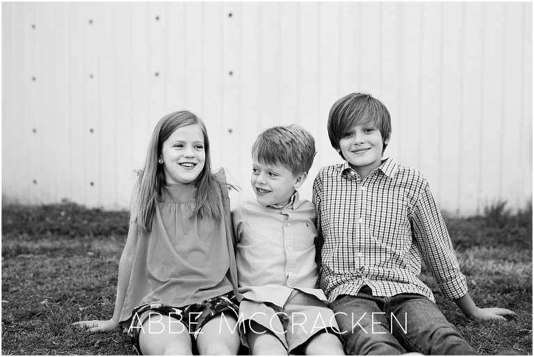 Candid black and white picture of three siblings taken during a family photography session