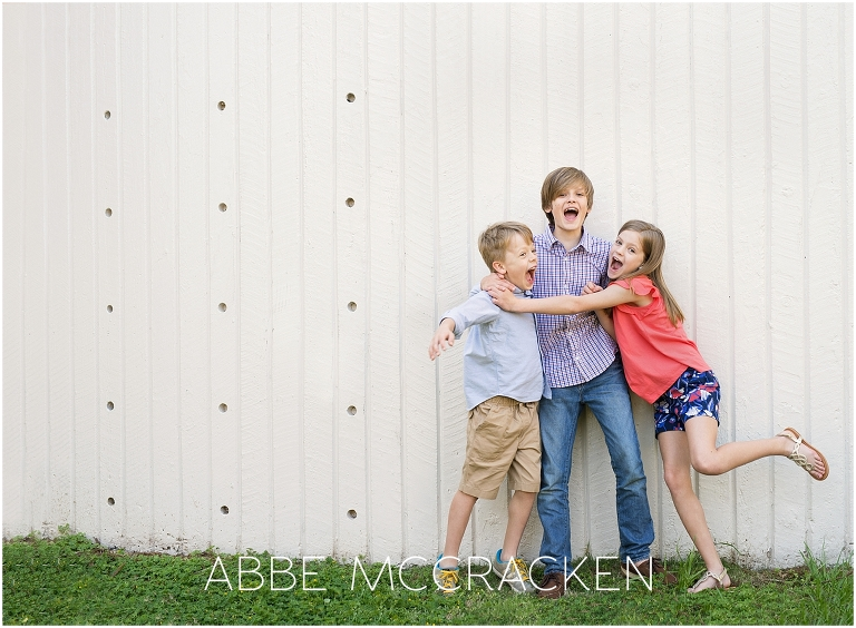 Candid picture of three joyful siblings taken during a family photography session