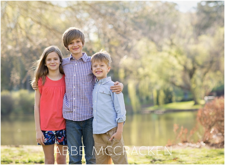 Three siblings posing for a picture during a family photography session in Charlotte's Freedom Park