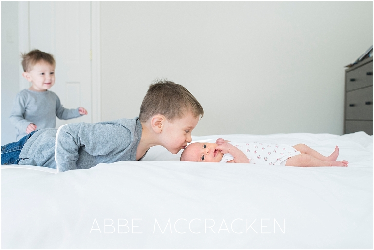 Newborn baby girl being admired by brothers | Newborn photography Charlotte NC