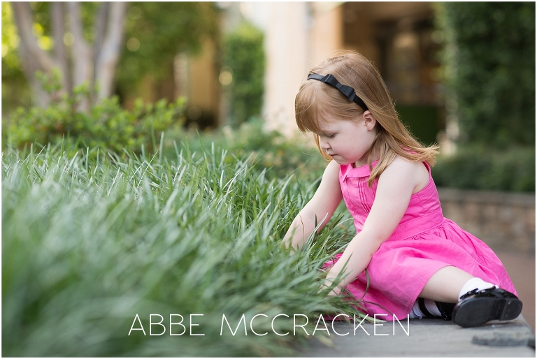 Picture of a young girl exploring tall grassed during spring family pictures on The Green in uptown Charlotte