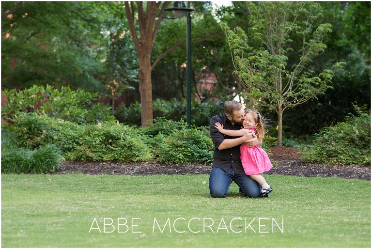 Candid, lifestyle family portraits in Uptown Charlotte - father hugging daughter