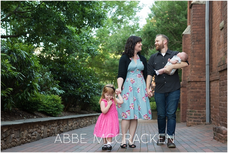 Family of four walking in Uptown Charlotte NC with a new baby and big sister