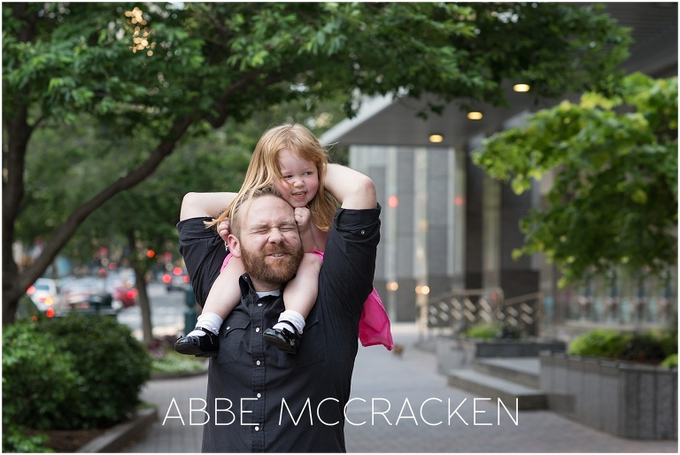 Candid picture of a young girl sitting on father's shoulders. Taken at the end of a family portrait session in Uptown Charlotte