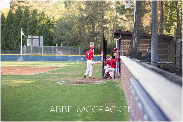 Candid dugout image of teamwork and camaraderie during high school baseball game