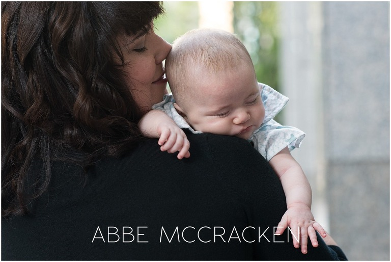 Image of a baby falling asleep on her mother's shoulder after a family photo session in uptown Charlotte, NC