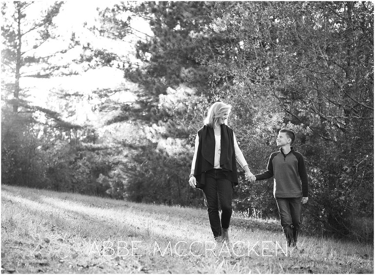 black and white, backlit photo of a mother and son walking, holding hands