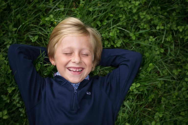 young boy laying in the grass and laughing