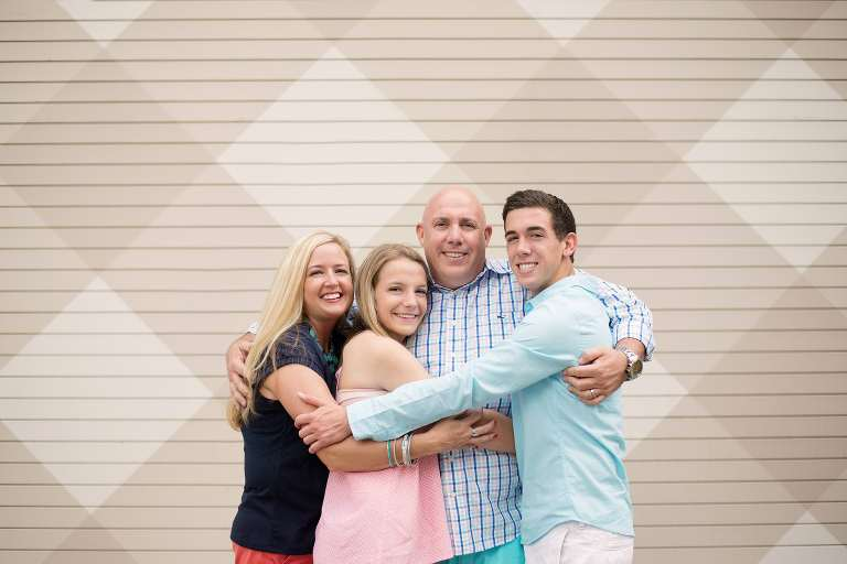 family of four with two teenage kids hugging and smiling for the camera