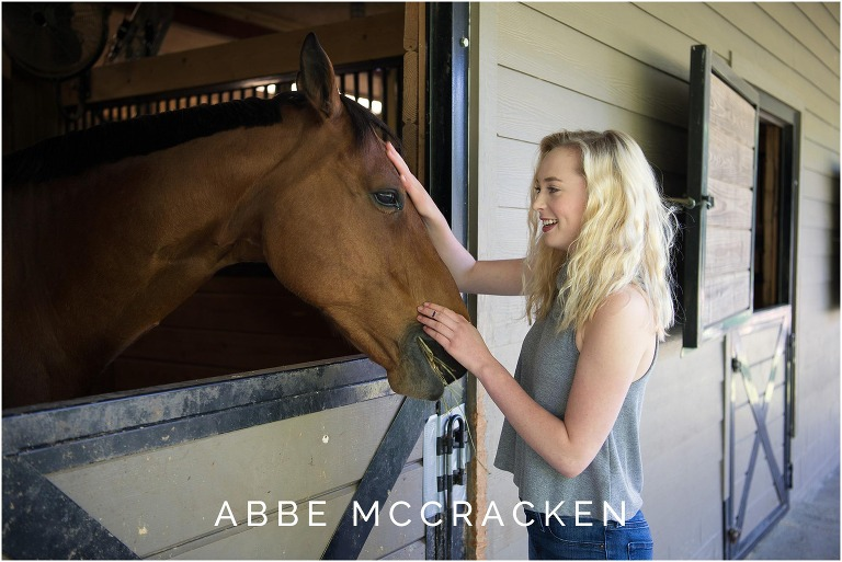High school senior petting her horse at the barn in Waxhaw, NC