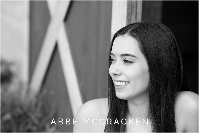Black and white high school senior portrait at barn in Marvin, NC