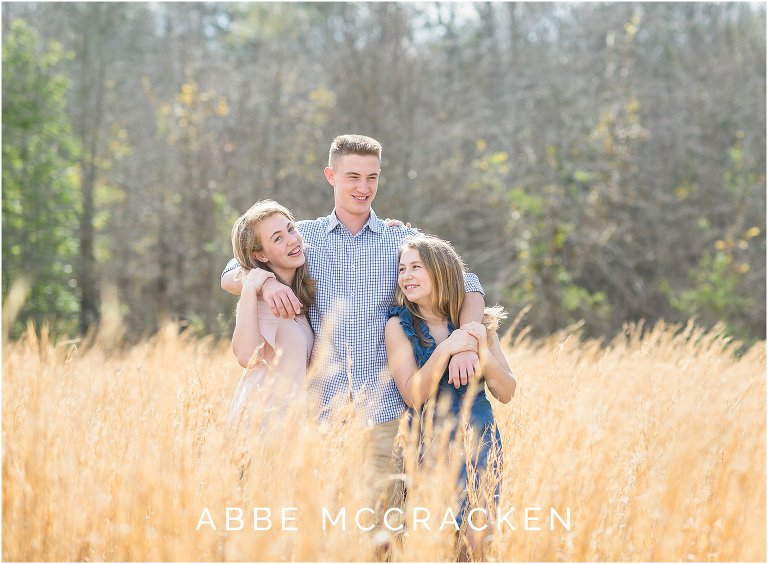 warm, sunny spring picture of siblings in a wheat field