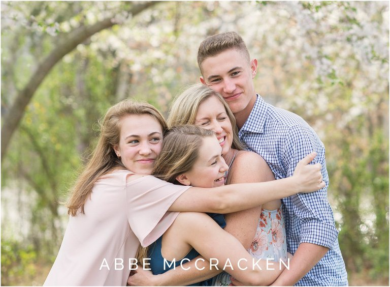 Candid image three teenage children hugging their mother - spring family session
