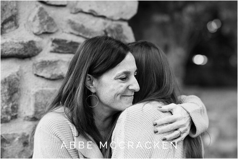 black and white emotional image of mother hugging her teenage daughter