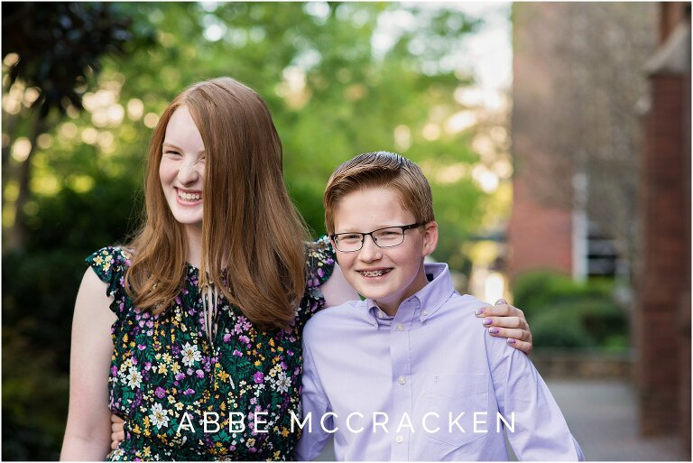 Red headed siblings laughing at each other during a spring family portrait session