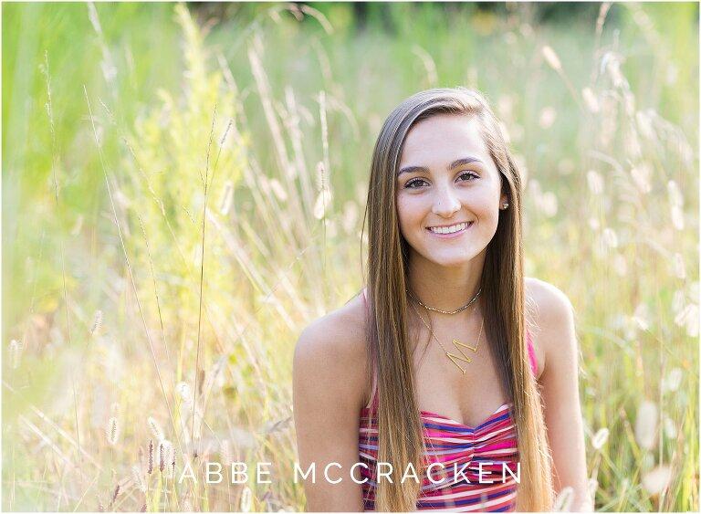 Summer portrait of a high school senior sitting amongst the tall wheat grasses near Charlotte, NC