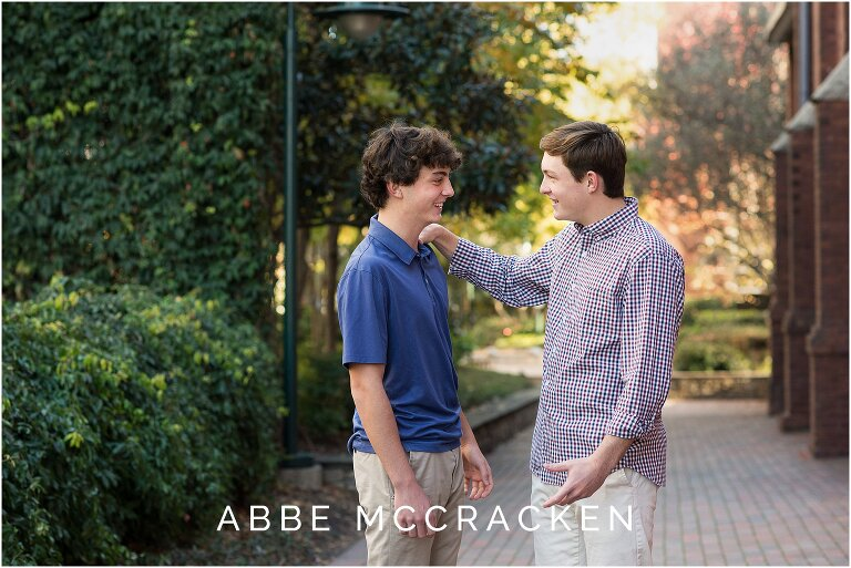 candid picture of teenage boy siblings teasing each other, photographed during a high school senior session