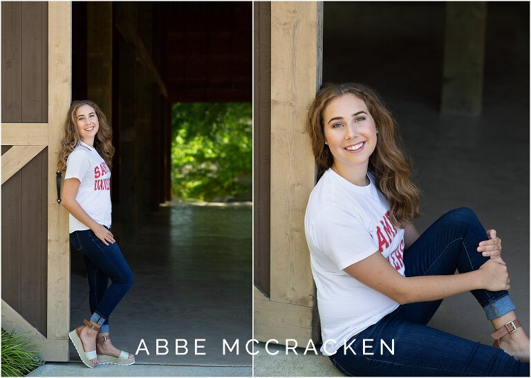 Girl standing and sitting against a barn for portraits in her college t-shirt, jeans and platform sandals