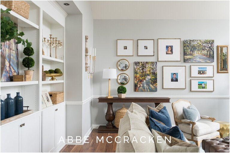 Interior design photography showcasing new built in bookcases and sofa leading to photo wall of family pictures